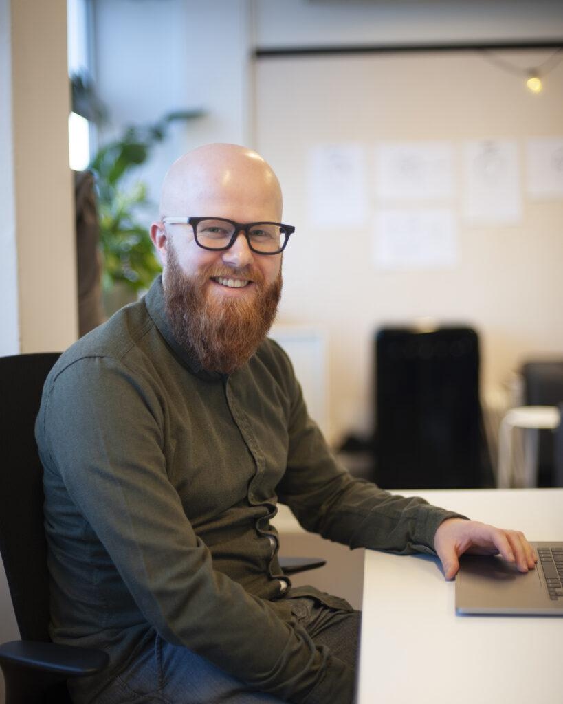 Mann med skjegg og briller sitter foran en datamaskin.